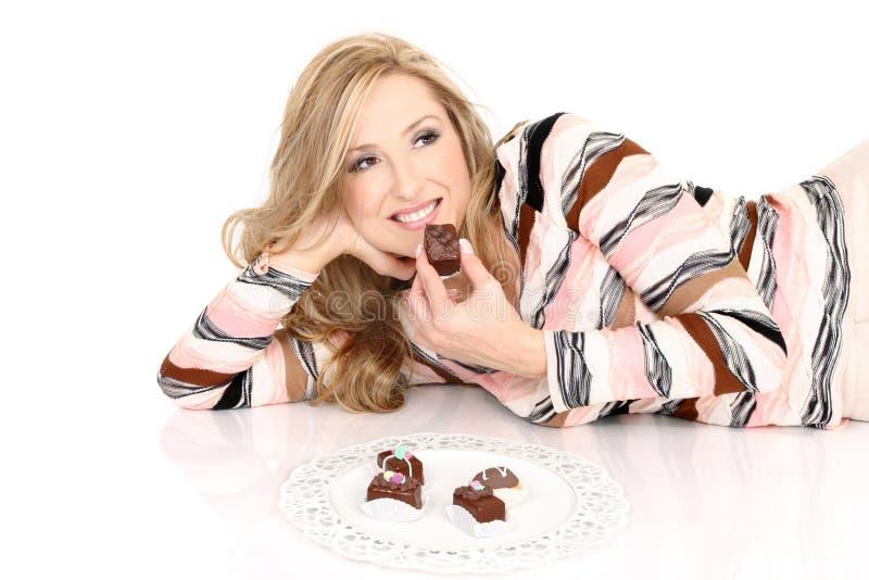 Muchacha que complace en chocolates imagenes de archivo