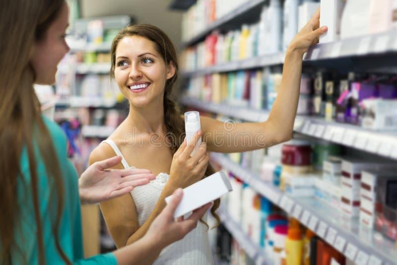 Muchacha que compra crema cosmética en la alameda de compras imagenes de archivo