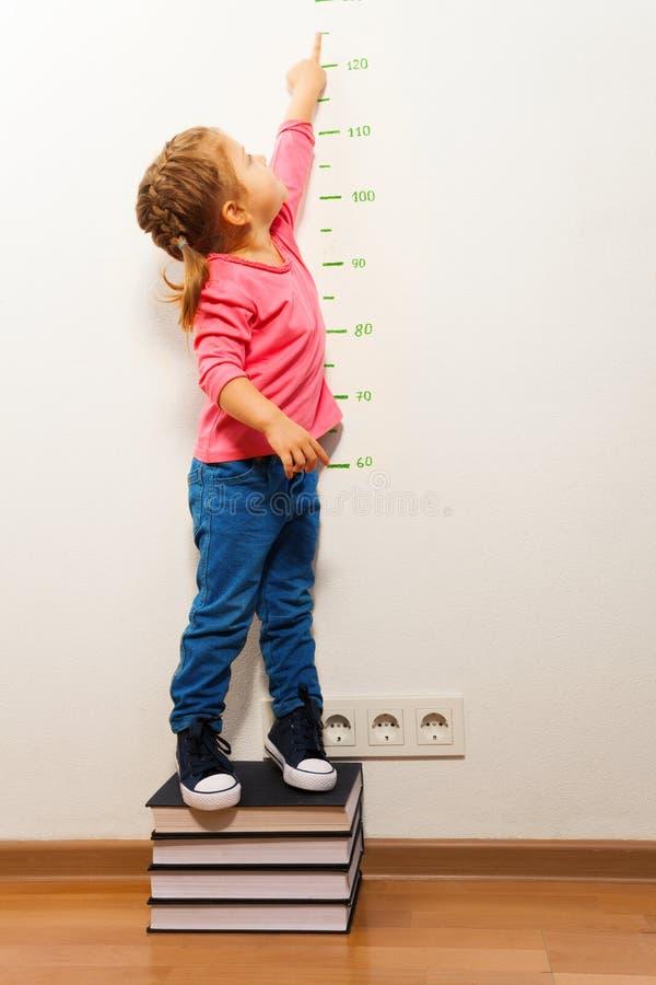 Muchacha que comprueba altura en carta de crecimiento en cuatro libros fotografía de archivo libre de regalías
