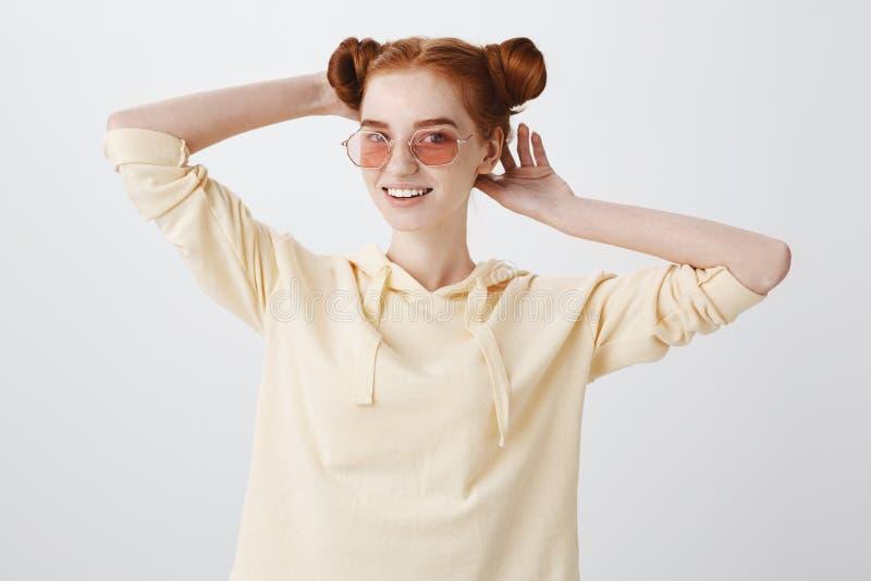 Muchacha que comprueba el corte de pelo, mirando en espejo El estudio tiró de estudiante joven elegante en gafas de sol de moda y fotografía de archivo