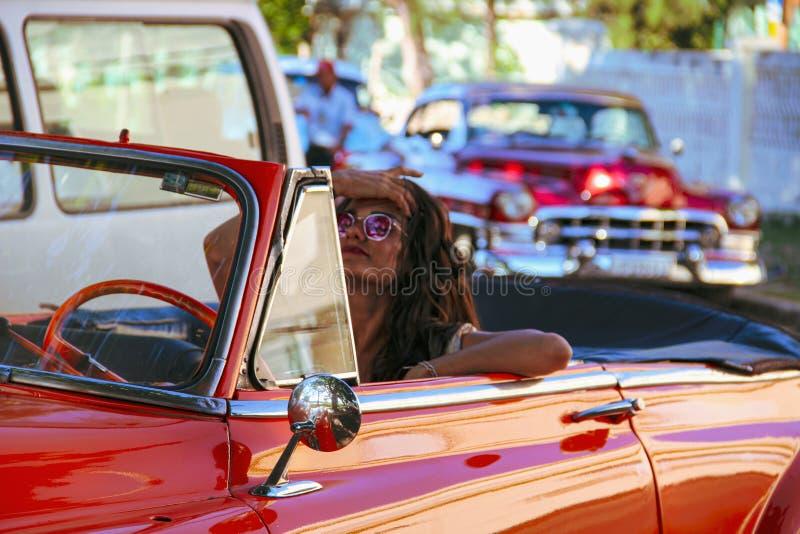 Muchacha que conduce el coche viejo en La Habana, Cuba foto de archivo libre de regalías