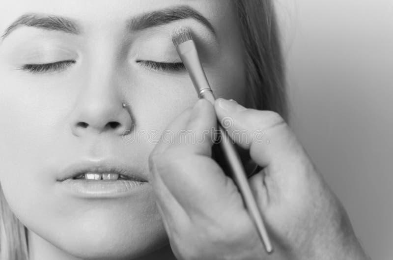 Muchacha que consigue el polvo del sombreador de ojos en los párpados con el cepillo fotos de archivo