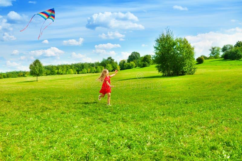 Muchacha que corre con la cometa fotografía de archivo libre de regalías
