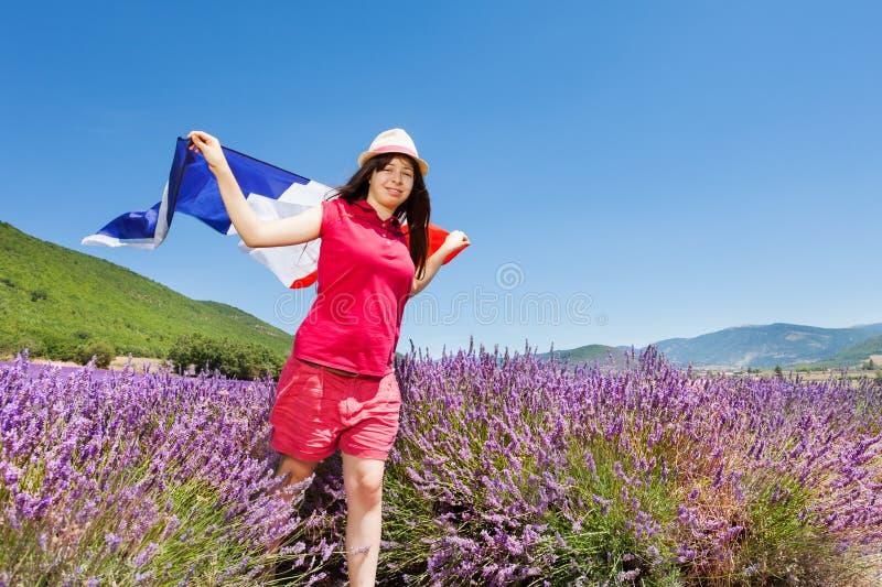 Muchacha que corre en campo de la lavanda con la bandera francesa foto de archivo libre de regalías