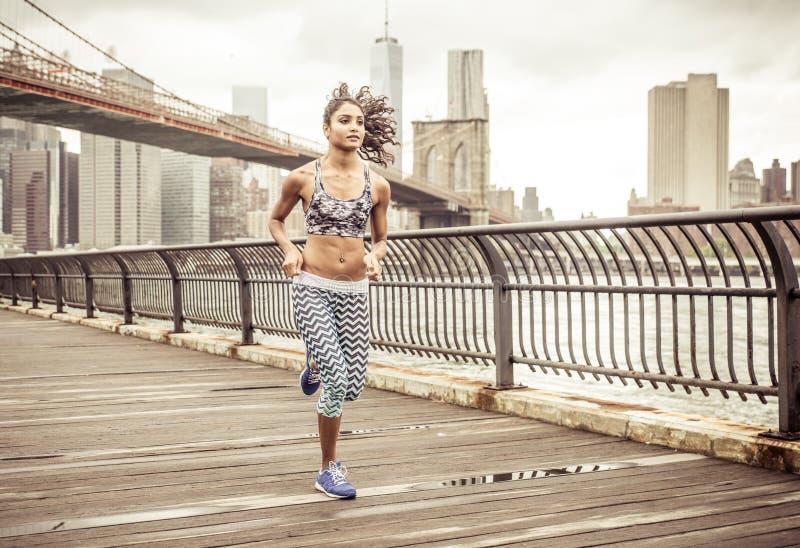 Muchacha que corre en el embarcadero con el horizonte de Nueva York fotos de archivo libres de regalías
