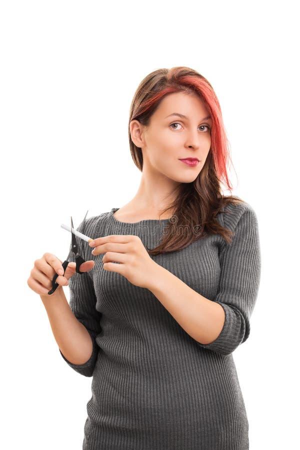 Muchacha que corta un cigarrillo con las tijeras fotos de archivo libres de regalías