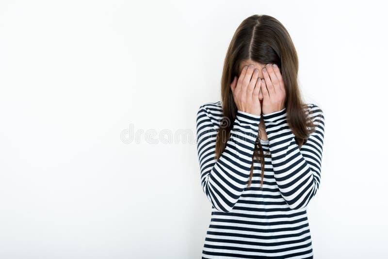 Muchacha que cubre su cara con las manos, concepto del embarressment fotos de archivo
