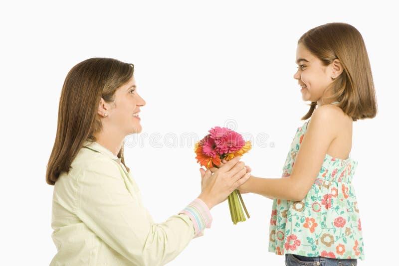 Muchacha que da las flores de la madre. foto de archivo