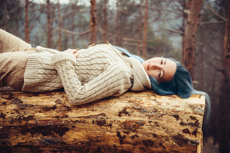 Muchacha que descansa sobre tronco de árbol fotos de archivo libres de regalías