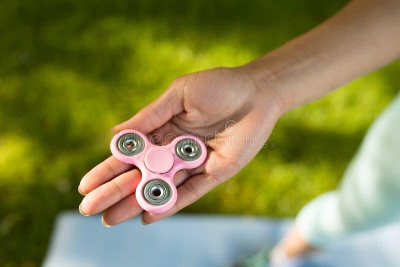 Muchacha que detiene a un hilandero de la persona agitada en un parque imágenes de archivo libres de regalías