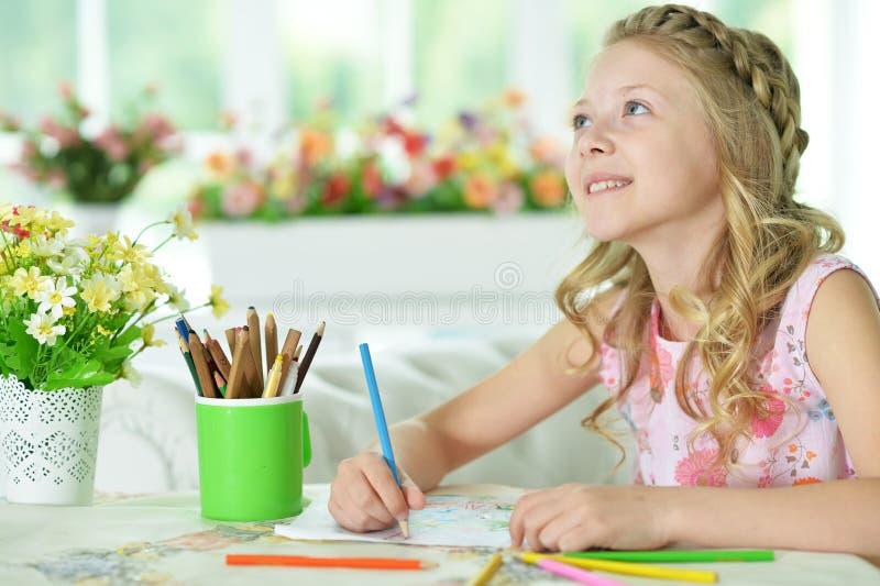 Muchacha que dibuja en casa imagenes de archivo