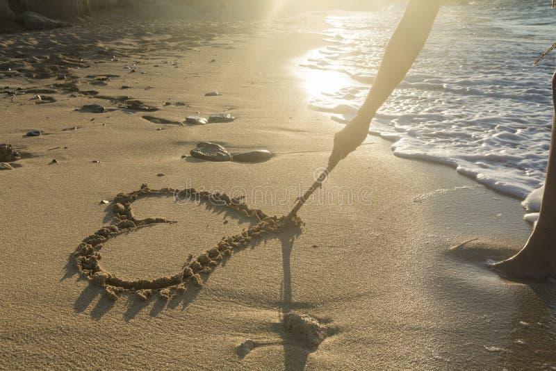 Muchacha que dibuja un corazón en la arena en la puesta del sol en un amor del verano concentrado imagen de archivo