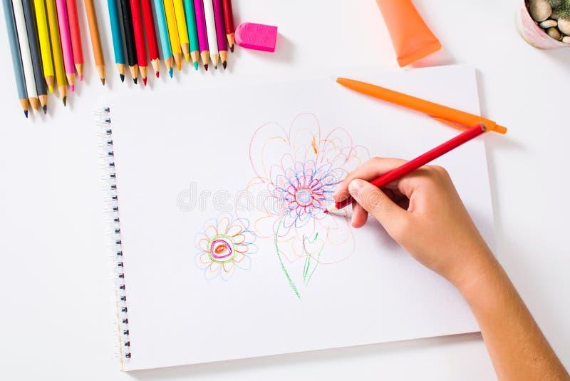 Muchacha que dibuja a una primera persona de la flor colorida foto de archivo libre de regalías