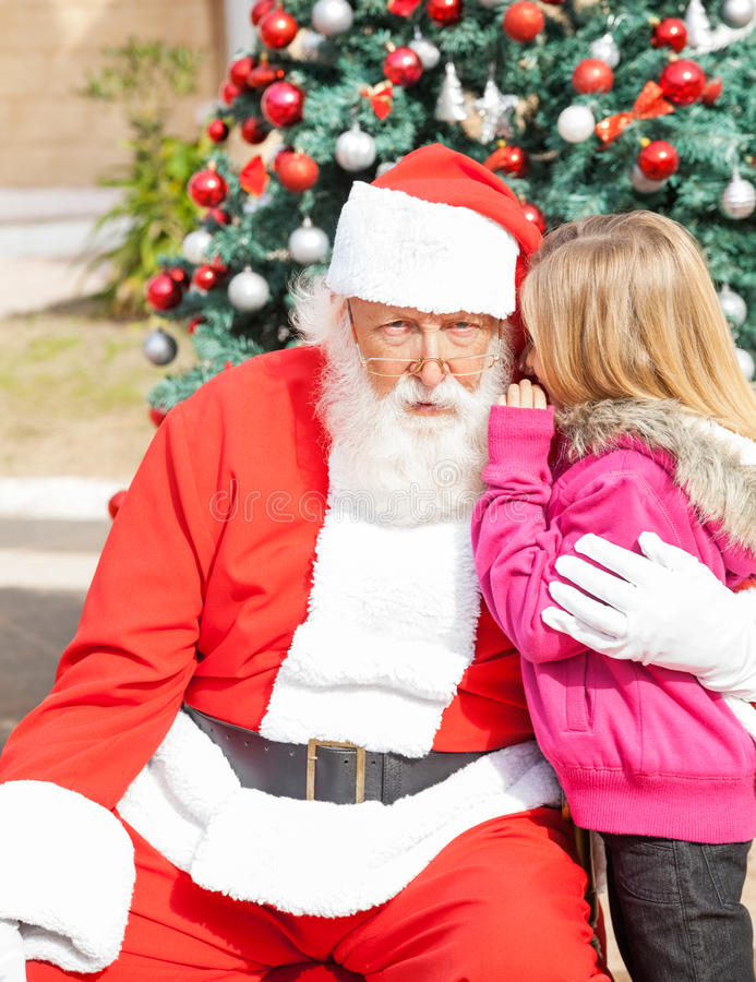 Muchacha que dice deseo en el oído de Papá Noel fotos de archivo libres de regalías