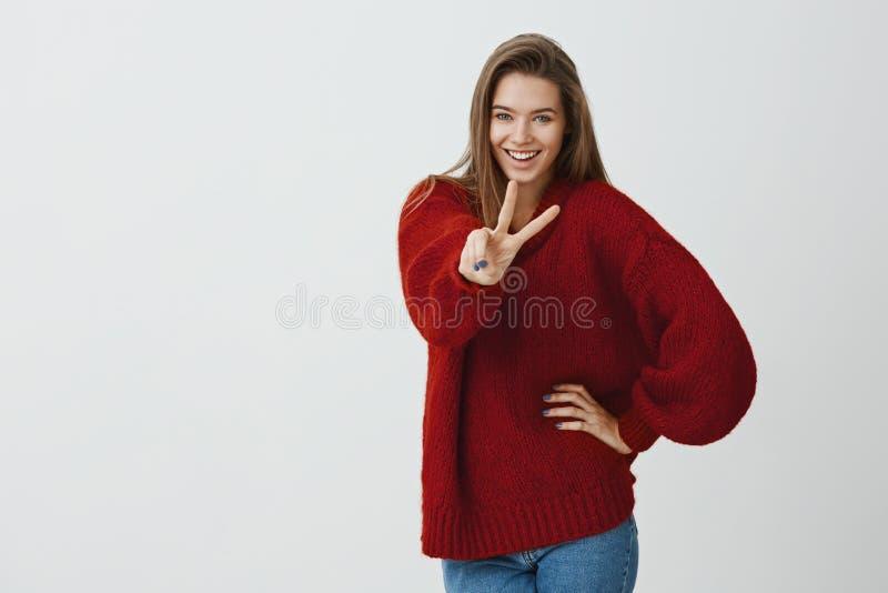 Muchacha que dice hola a las aventuras Tiro interior de la hembra europea atractiva en suéter rojo flojo de moda, mostrando la vi foto de archivo