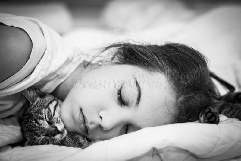 Muchacha que duerme con el gato ninguna alergia fotografía de archivo