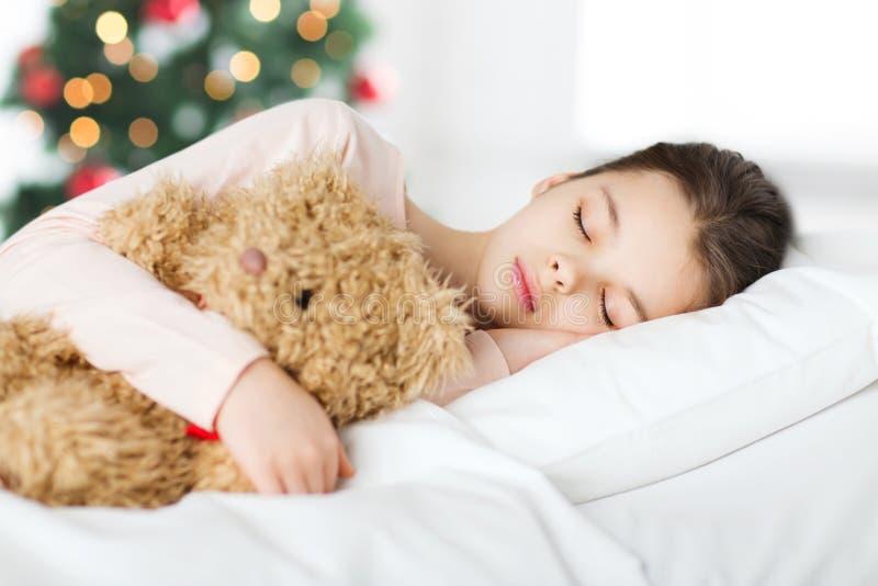 Muchacha que duerme con el oso de peluche en cama en la Navidad foto de archivo