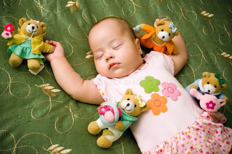 Muchacha que duerme con los juguetes fotografía de archivo