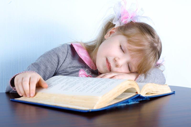 Muchacha que duerme en el libro foto de archivo