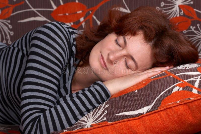 Muchacha que duerme en el sofá anaranjado fotografía de archivo libre de regalías