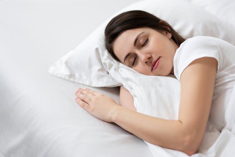 Muchacha que duerme en la cama blanca foto de archivo