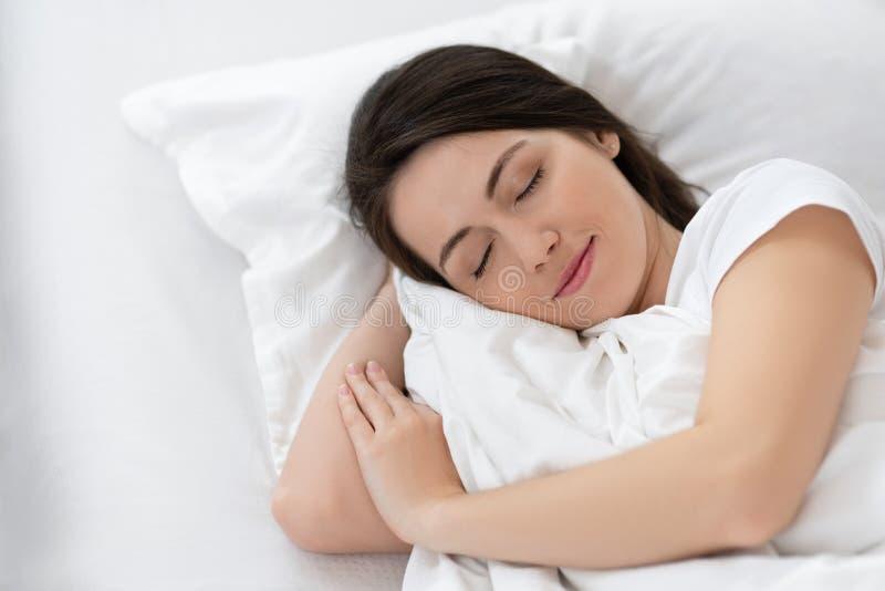 Muchacha que duerme en la cama blanca fotografía de archivo