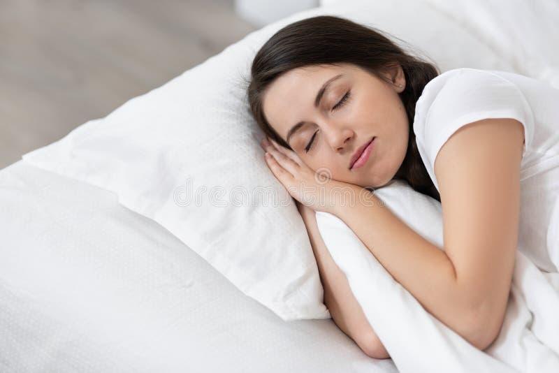 Muchacha que duerme en la cama blanca imagen de archivo