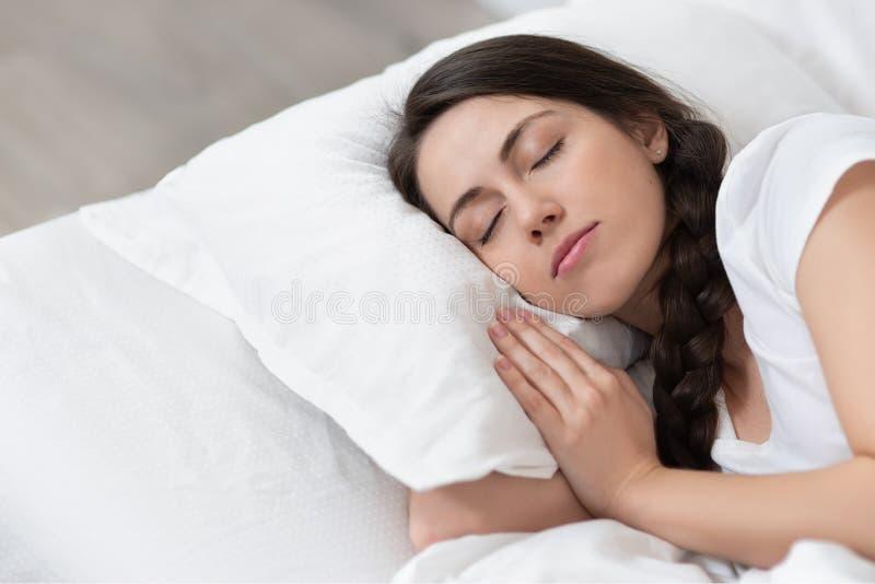 Muchacha que duerme en la cama blanca imagen de archivo libre de regalías