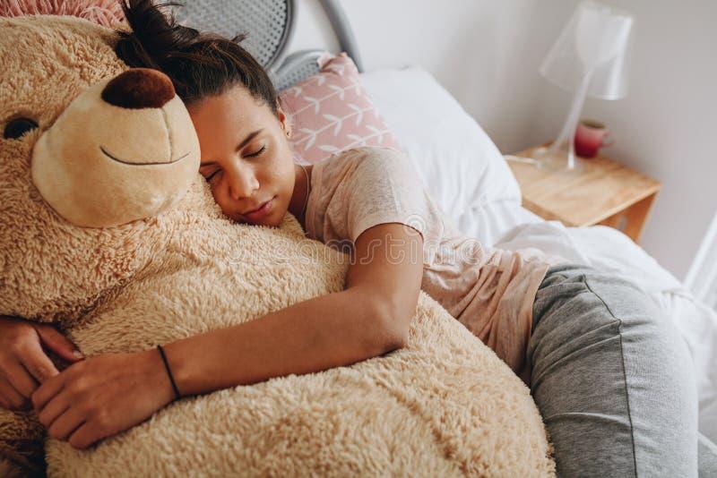 Muchacha que duerme en la cama que sostiene un oso de peluche fotos de archivo