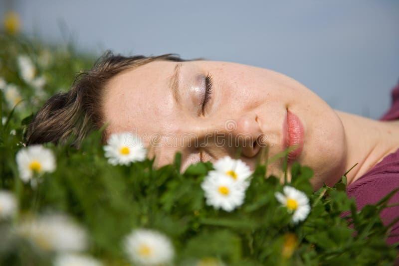 Muchacha que duerme en la hierba fotos de archivo