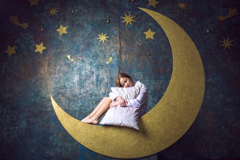 Muchacha que duerme en la luna imagenes de archivo