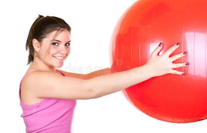 muchacha que ejercita con la bola roja grande fotografía de archivo