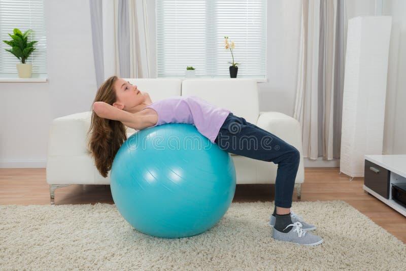 Muchacha que ejercita en la bola de Pilates foto de archivo
