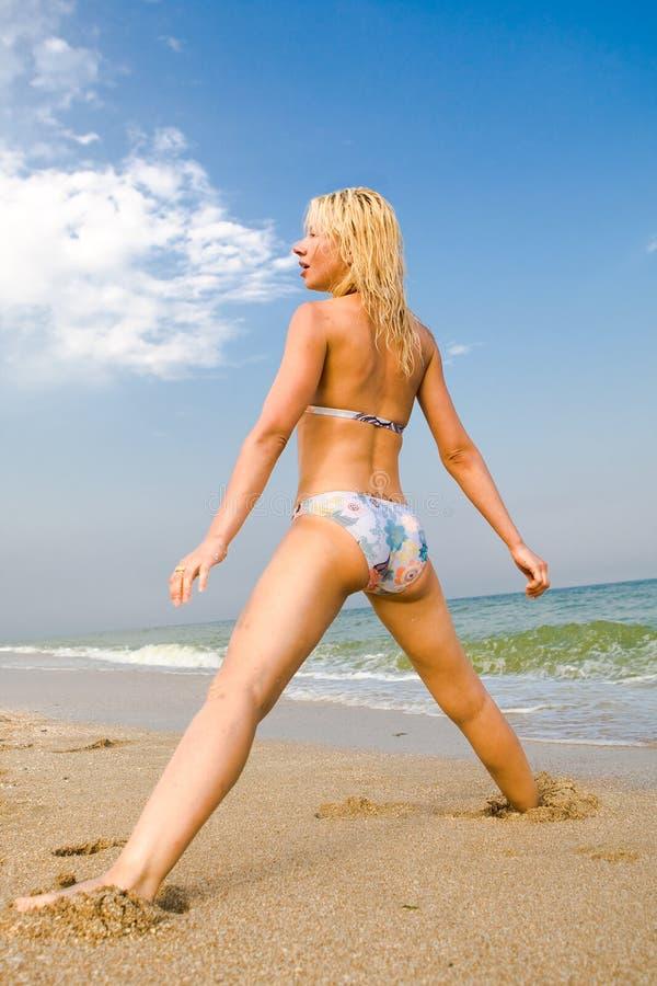 Muchacha que ejercita en la playa del mar imagen de archivo