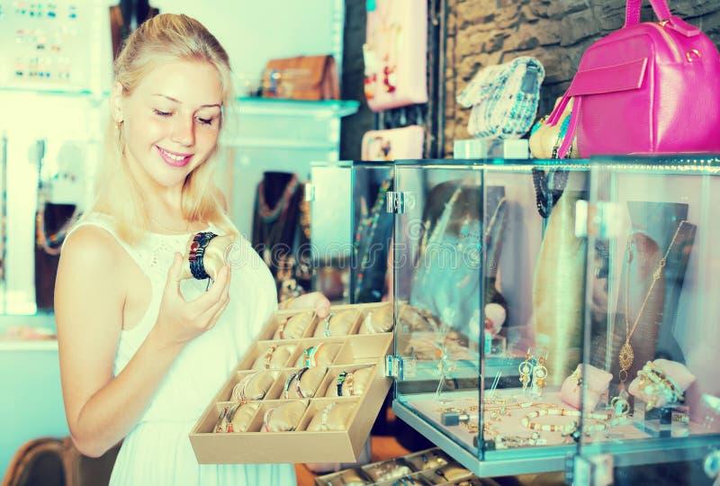 Muchacha que elige la pulsera en tienda del bijouterie fotografía de archivo libre de regalías