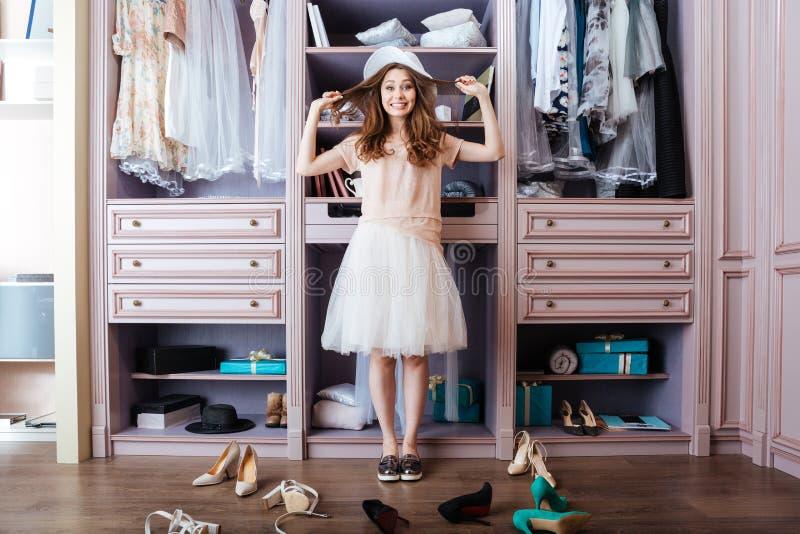 Muchacha que elige los zapatos en su guardarropa imagenes de archivo
