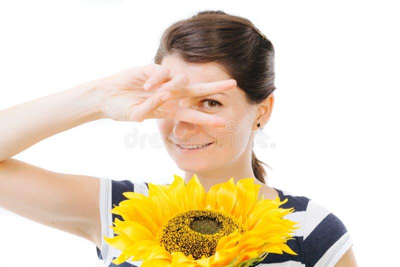 Muchacha que es divertida, sosteniendo un girasol imagenes de archivo