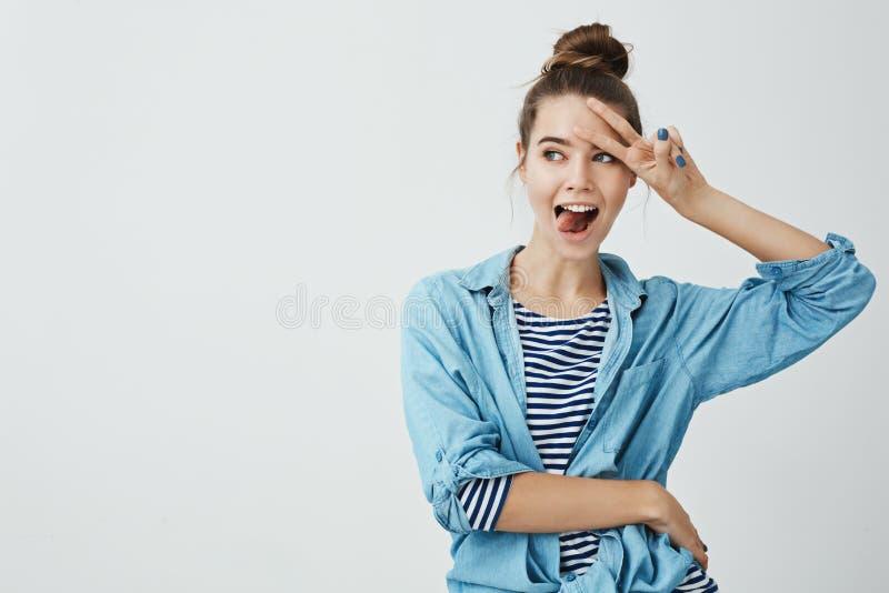 Muchacha que es en lado positivo toda la hora El retrato de la mujer atractiva alegre con el peinado del bollo que lleva a cabo v fotos de archivo