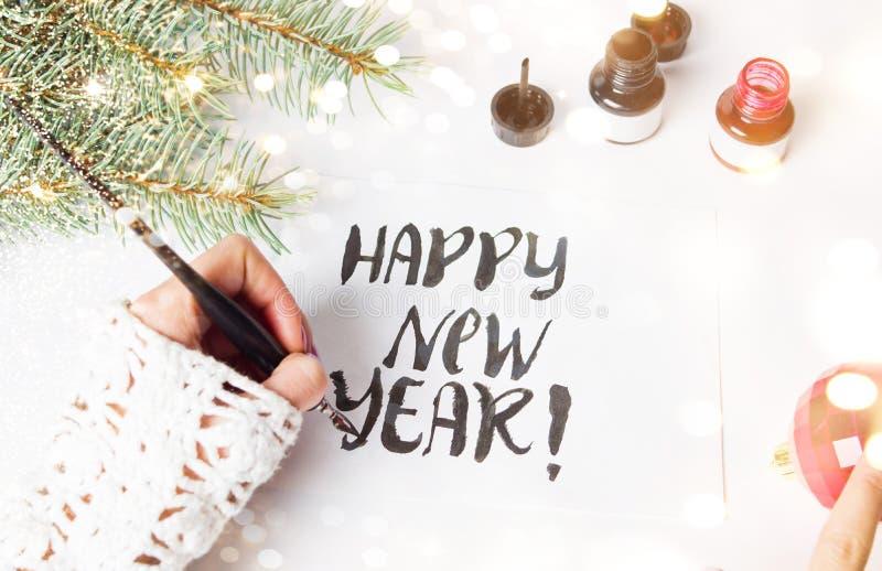 Muchacha que escribe la tarjeta de la caligrafía de la Feliz Año Nuevo imagen de archivo