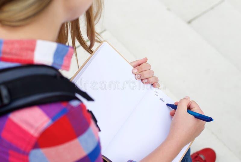 Muchacha que escribe a para hacer la lista en libro fotos de archivo libres de regalías