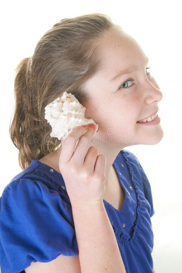 Muchacha que escucha el seashell fotografía de archivo libre de regalías