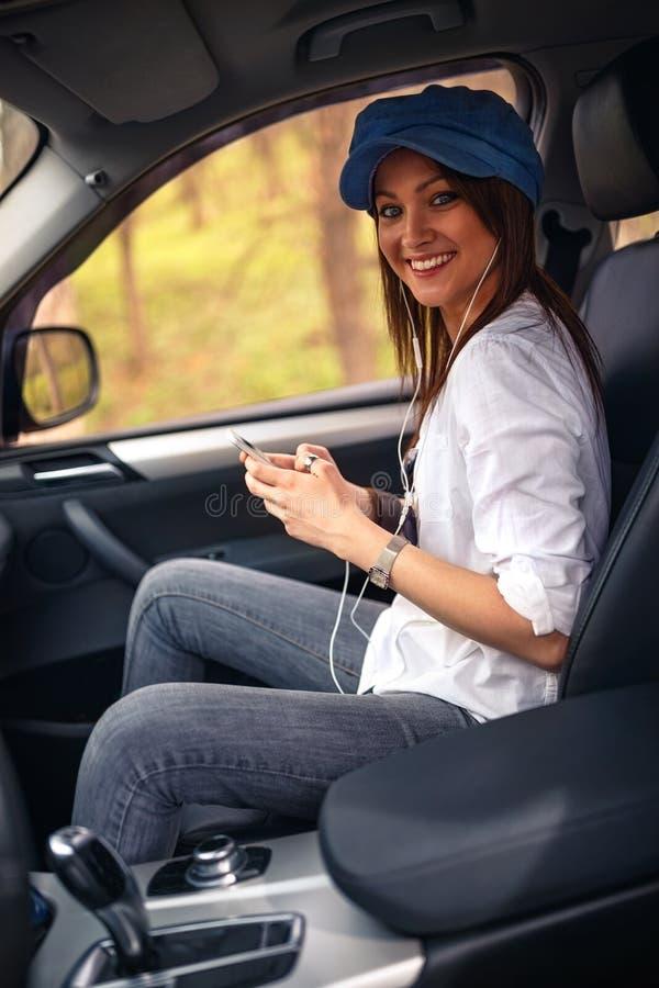 Muchacha que escucha la música con los auriculares que se mueven en coche imágenes de archivo libres de regalías