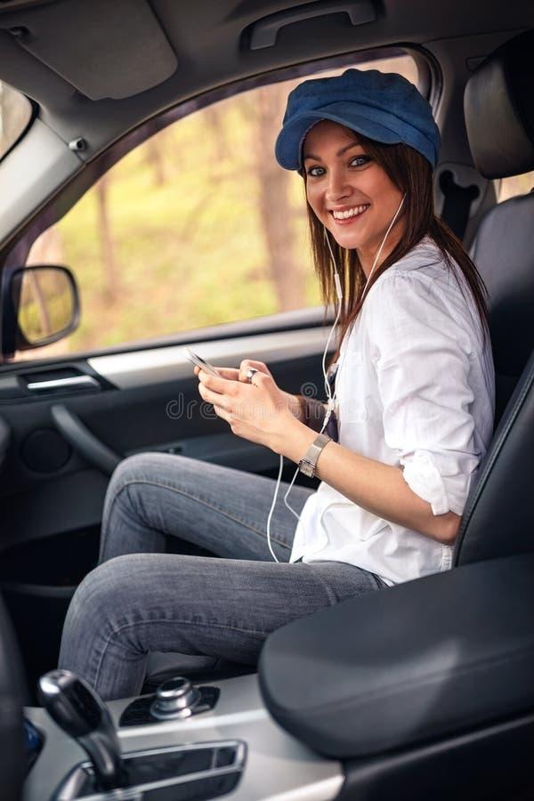 Muchacha que escucha la música con los auriculares que se mueven en coche foto de archivo