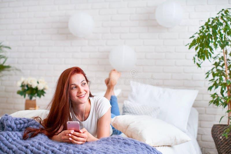 Muchacha que escucha la música en auriculares en cama luz brillante de la mañana del dormitorio de las ventanas fotografía de archivo