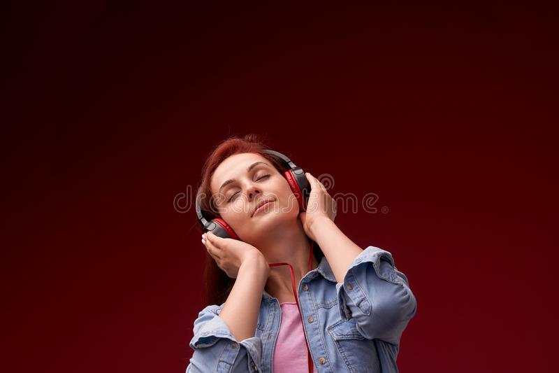 Muchacha que escucha la m?sica en auriculares muchacha hermosa joven pelirroja en vaqueros y la sonrisa feliz de la camiseta en a imagen de archivo