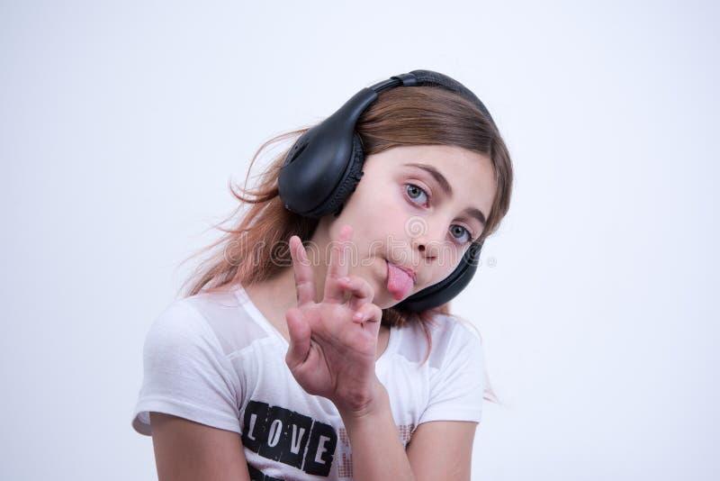 Muchacha que escucha una música en el auricular que hace una muestra de paz y de amor fotos de archivo libres de regalías