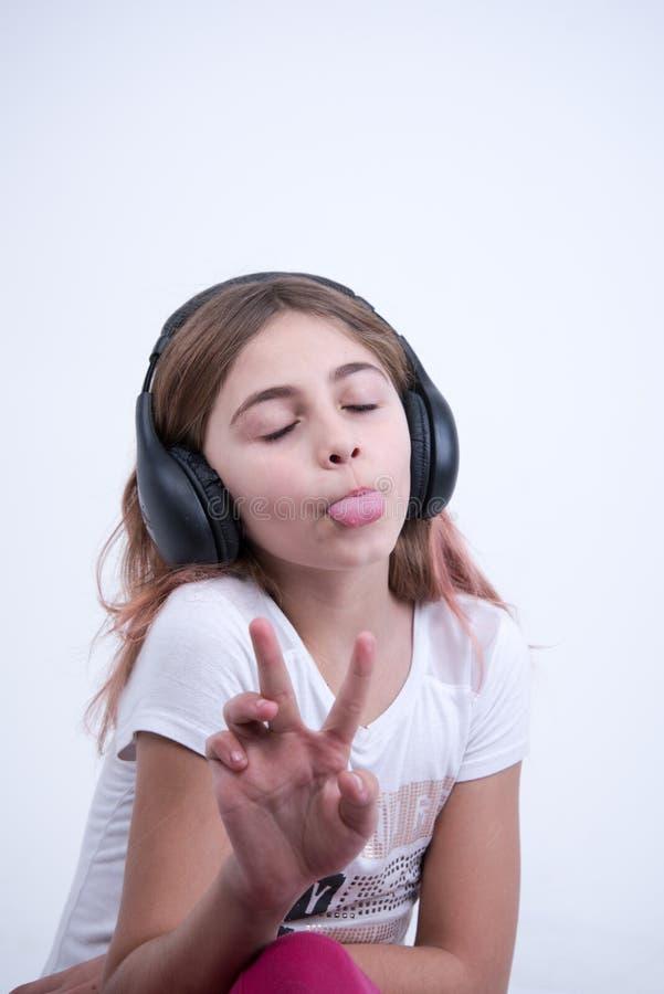 Muchacha que escucha una música en el auricular que hace una muestra de paz y de amor imagen de archivo libre de regalías