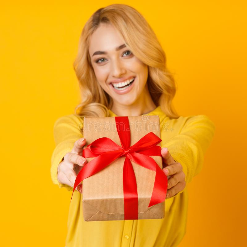 Muchacha que estira la caja de regalo a la cámara sobre fondo amarillo imágenes de archivo libres de regalías