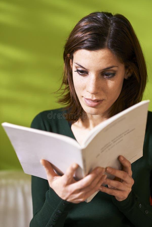 Muchacha que estudia la literatura con el libro en casa foto de archivo