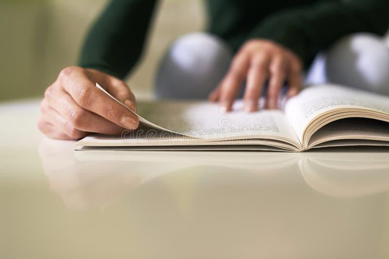 Muchacha que estudia la literatura con el libro en casa imagenes de archivo